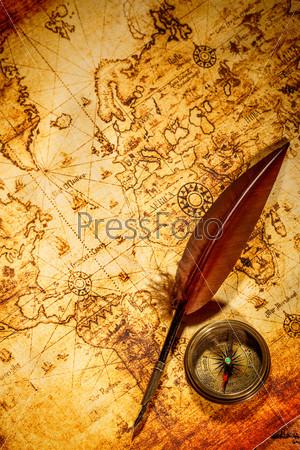 Старинный компас и гусиное перо лежат на старой карте
