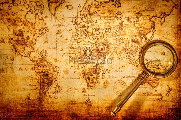 Винтажное увеличительное стекло лежит на карте древнего мира