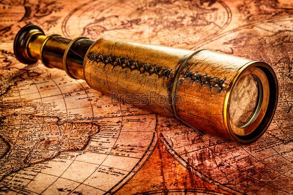 Фотография на тему Старинная подзорная труба лежит на карте древнего мира