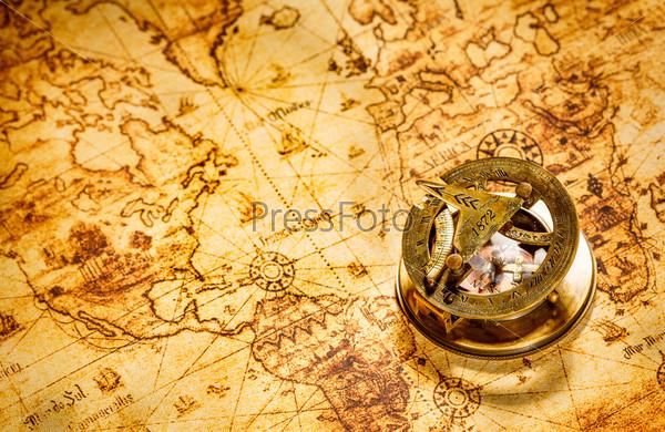 Старинный компас лежит на карте древнего мира