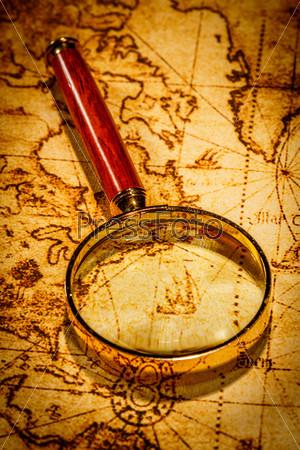 Старинное увеличительное стекло лежит на карте древнего мира