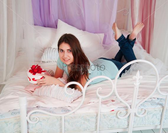 Женщина в постели, открывает подарок