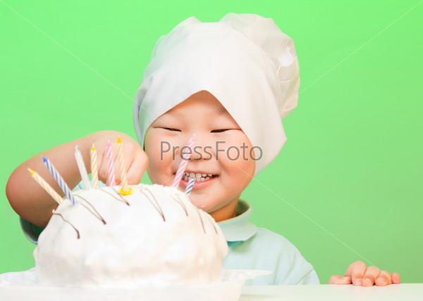 Мальчик ставит свечи в торт на день рождения
