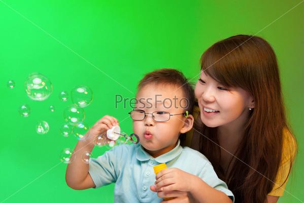 Мать и сын делают мыльные пузыри