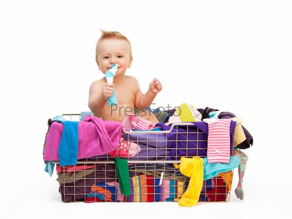 Малыш, сидящий в корзине с одеждой