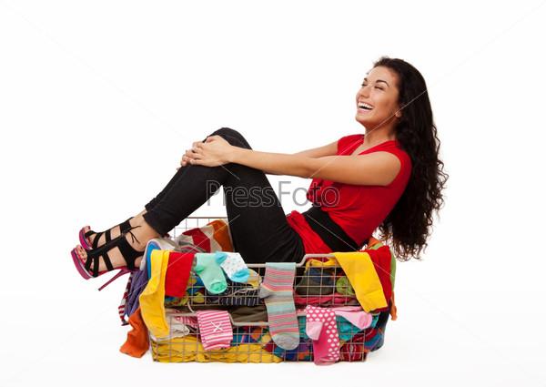 Женщина, сидящая в корзине с одеждой