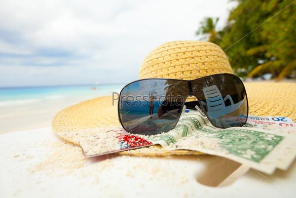 Соломенная шляпа, деньги и очки на пляже