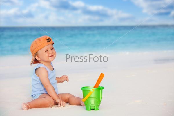 Ребенок играет с песком на пляже