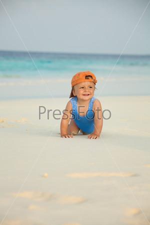 Фотография на тему Счастливый ребенок ползет по пляжу