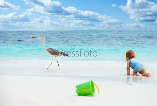 Счастливый ребенок играет на пляже