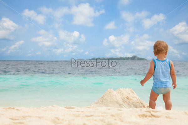 Малыш играет на песчаном пляже