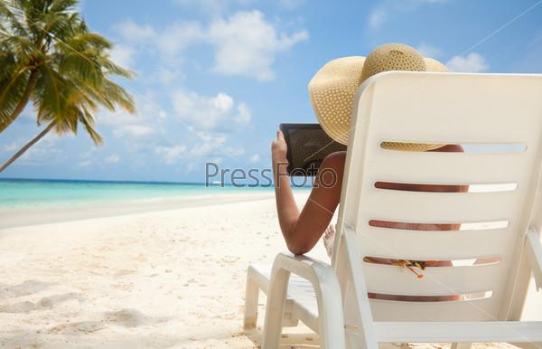 Женщина с планшетным компьютером на пляже
