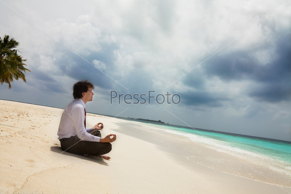 Бизнесмен медитирует, сидя на песчаном пляже