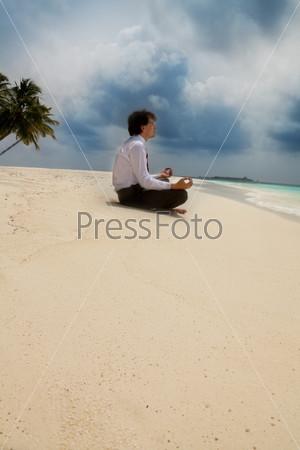 Фотография на тему Бизнесмен медитирует, сидя на песчаном пляже