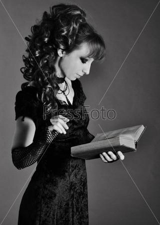 Черно-белая фотография девушки со старинной книгой в руках