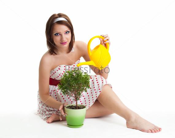 Женщина поливает растение