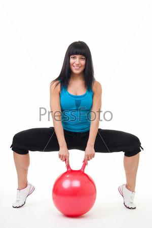 Молодая счастливая женщина тренируется с мячом