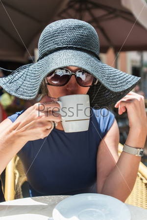 Женщина пьет кофе в уличном кафе