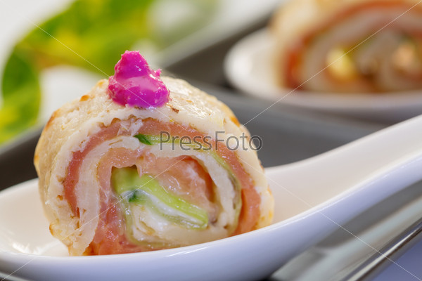 Фотография на тему Роллы с копченым лососем, огурцом и крем-фреш на белой ложке крупным планом
