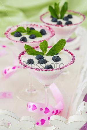 Фотография на тему Свежий чернично-йогуртный десерт в бокале для мартини с листьями мяты для украшения