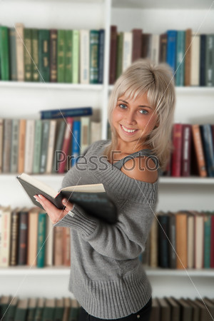 Женщина стоит возле книжного шкафа
