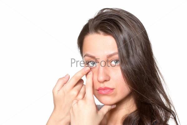 Фотография на тему Молодая женщина одевает контактные линзы