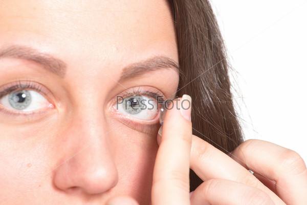 Молодая женщина одевает контактные линзы