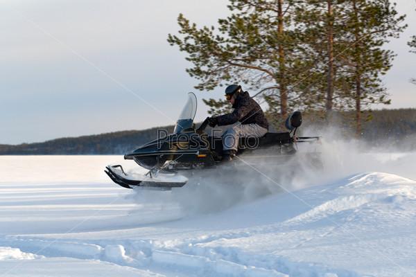 Человек едет на снегоходе