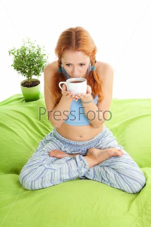 Фотография на тему Молодая женщина в позе йога пьет чай