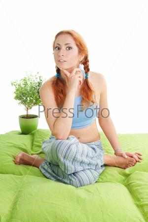Рыжеволосая женщина в позе йоги на диване
