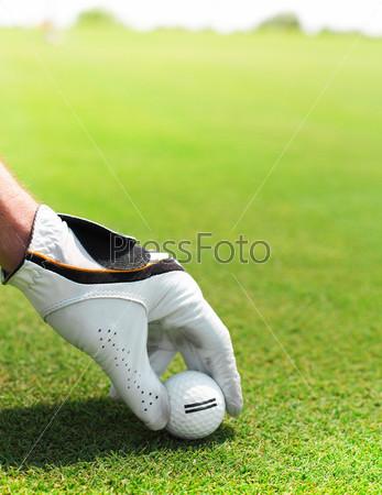 Фотография на тему Рука гольфиста держит мяч