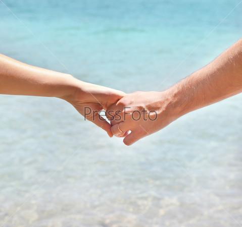 Молодая влюбленная пара гуляет, взявшись за руки