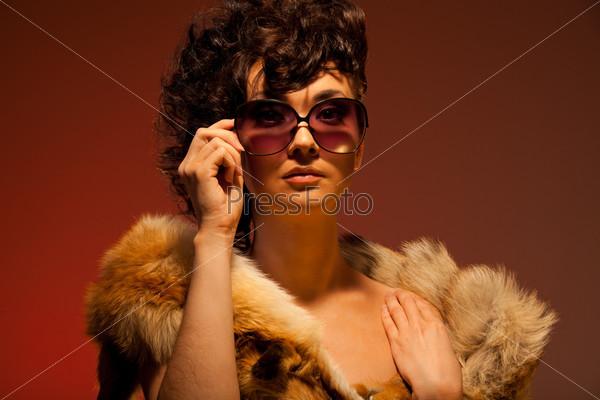Фотография на тему Великолепная женщина в солнцезащитных очках и меховой горжетке