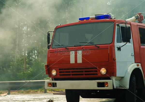 Пожарная машина на пожаре с дымом на заднем плане