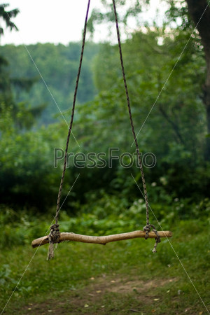 Фотография на тему Качели в летнем лесу символизируют мир, спокойствие, но одиночество