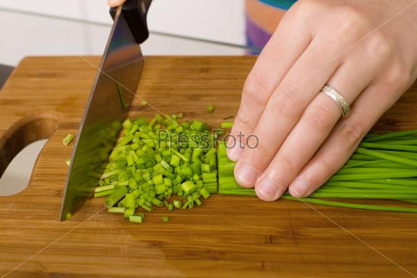 Нарезка зеленого лука ножом на деревянной доске
