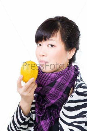 Спокойно улыбающаяся азиатская женщина держит лимон, глядя на камеру