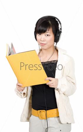 Азиатская женщина учится с помощью наушников и желтой книги