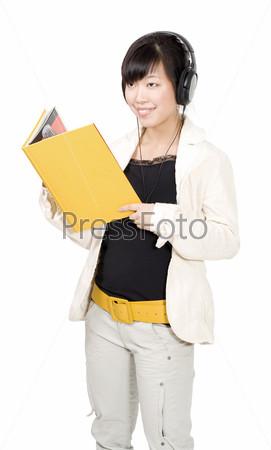 Азиатская женщина стоит с желтой книгой и стушает музыку в наушниках