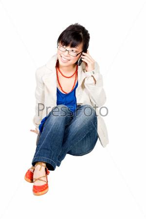 Улыбающаяся азиатская девушка в очках говорит по мобильному телефону