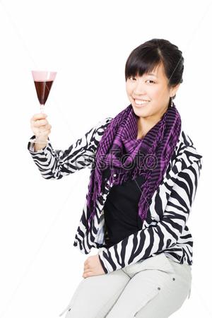Азиатская женщина пьет вино из фиолетового бокала на белом фоне
