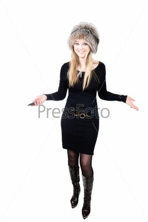 Русская светловолосая женщина в меховой шапке говорит по мобильному телефону