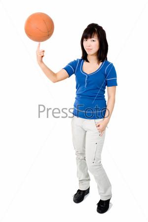 Азиатская женщина крутит баскетбольный мяч на пальце