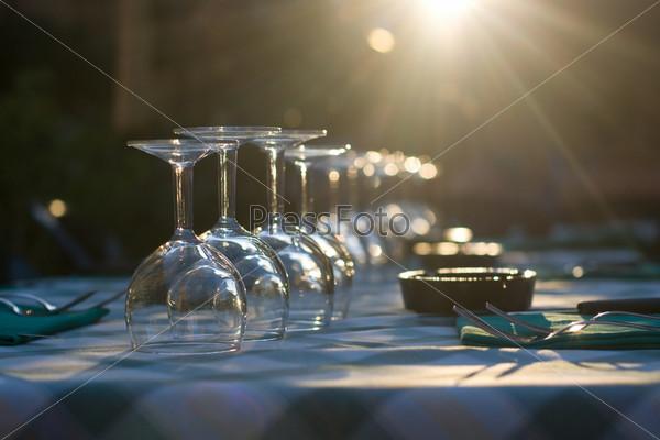 Очки и посуда на столике в ресторане в лучах света