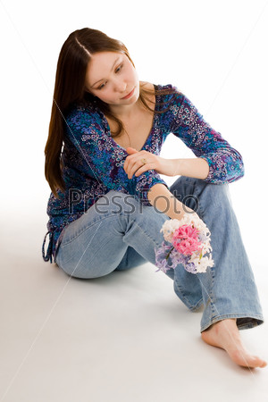 Романтичная женщина с цветком в руке сидит на полу, глядя вниз