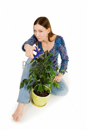 Женщина обрезает растение синими ножницами, сидя на полу
