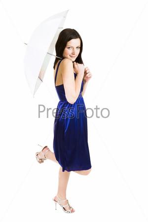 Молодая красивая женщина с зонтиком в синем платье стоит на одной ноге