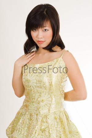 Фотография на тему Милая азиатская женщина в золотом вечернем платье привлекательным взглядом