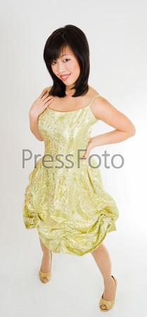 Красивая молодая азиатская женщина стоит в золотом платье и улыбается