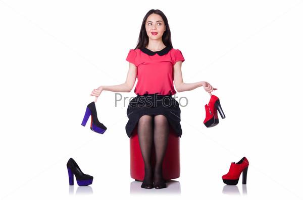Молодая женщина с выбором обуви на белом фоне